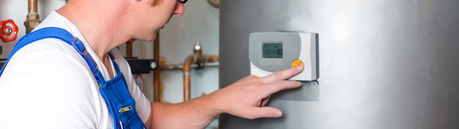 Heizungs und Sanitärtechniker kontrolliert Thermostat